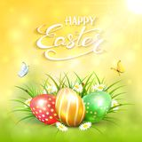 Yellow sunny background with Easter eggs in grass Stock Images
