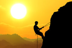 On the yellow sunset background. Silhouette of man climbing on rock (mountain) at sunset Royalty Free Stock Images