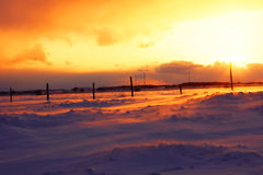 Yellow sunset over snowbank Royalty Free Stock Image