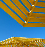 Yellow sunshade and blue sky Royalty Free Stock Photo