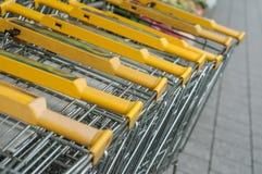 Yellow supermarket trolleys alignment. Closeup of yellow supermarket trolleys alignment Royalty Free Stock Photography