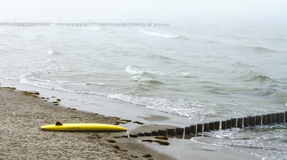 Yellow surf board lying at the shore Stock Images