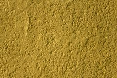 Yellow surface of a concrete wall with deep reliefs and shadows. rough texture. A yellow surface of a concrete wall with deep reliefs and shadows. rough texture stock images