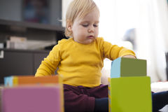 Yellow sweater baby placing boxes Stock Photo