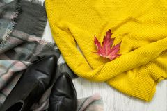 Yellow sweater, black boots and scarf. Red maple leaf. Fashionable concept stock image