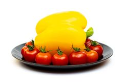 Yellow sweet pepper with tomatoes in a black plate isolated on white background. Composition of yellow peppers and red tomatoes on stock photo