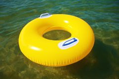 Yellow swim ring floating Stock Photos