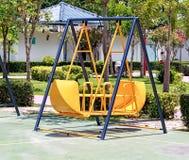 Yellow Swing in Children Playground Stock Photo