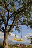 Yellow swing,3. A yellow swing hanging on a tree  on a beautiful sunny day,blue sky Stock Photo