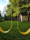 Yellow swing seats on backyard play structure. And green grass Stock Images