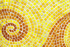 Yellow swirl pattern tiled bathroom wall. Mini square tiles background Stock Photos