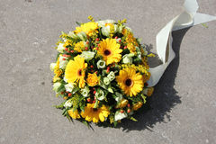 Yellow sympathy flowers. On a tombstone Royalty Free Stock Photo