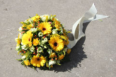 Yellow sympathy flowers. On a tombstone Stock Image