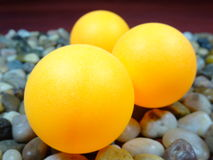 Yellow table tennis balls. 3 yellow table tennis balls in river rock background Royalty Free Stock Images