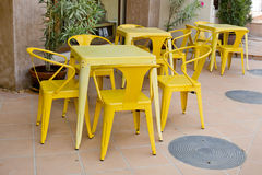 Yellow tables and chairs at outdoor restaurant Stock Photo