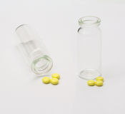 Yellow tablets and empty bottle Stock Photography