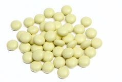 Yellow tablets with a jar. Heap of yellow tablets on a white background it is isolated Stock Images