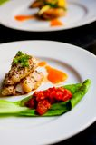 Yellow tail fillet dine. Yellow tail fillet, carrot puree and braised bak choy and tomato Royalty Free Stock Photography