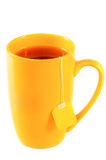 Yellow tall mug of tea with a label Royalty Free Stock Photos