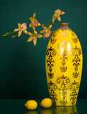 Yellow tall vase with flowers and two lemons Royalty Free Stock Image