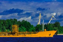 Yellow tanker ship. Yellow cargo tanker ship moving at the clear summer day Stock Photo