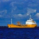 Yellow tanker ship. Yellow cargo tanker ship moving at the clear summer day Stock Image