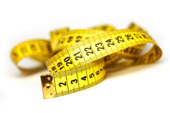 Yellow tape. Whirled yellow tape measure on white background Stock Photo