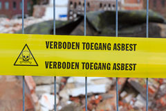 Yellow tape on fence with Dutch text 'no entry asbestos'. In front of demolition site stock image