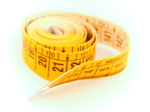Yellow tape measure. Closeup with a yellow tape measure on a white background stock photos
