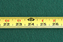 Yellow tape measure. Yellow tape measuring five inches on a green table Stock Photos