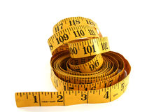 Yellow Tape Measure. Closeup with a yellow tape measure on a white background stock images
