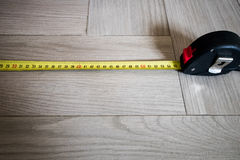 Yellow Tape measure. Measuring 55 cm on a parquet or porcelain st stock images