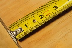 Yellow tape measure measuring a piece of wood Royalty Free Stock Photos