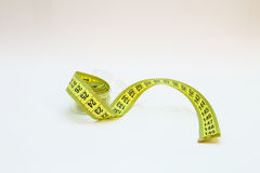 Yellow tape measure in meters and inches in a spiral Royalty Free Stock Photo
