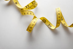 Yellow tape measure in meters and inches in a spiral Stock Image