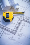 Yellow tapeline and blueprints Royalty Free Stock Images