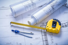 Yellow tapeline compass and rolls of blueprints Royalty Free Stock Photo