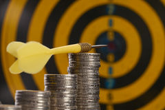 Yellow target dart with arrow on pile of coins. Can be used as business idea or energy saving concept. Target marketing or target arrow concept Royalty Free Stock Images