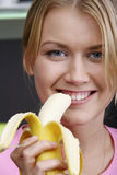 Yellow taste. Portrait of young pretty woman eating the banana Stock Image
