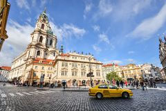 Yellow Taxi And Ancient Church Of Saint Nicholas In The Lesser Town Of Prague, Czech Republic Stock Photos