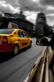 Yellow Taxi. Yellow cab chased by black car in motion blur speed traffic Royalty Free Stock Photos