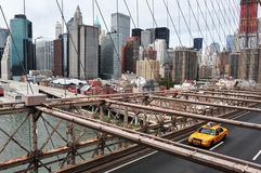 Yellow taxi cab crossing Brooklyn Bridge Stock Photo