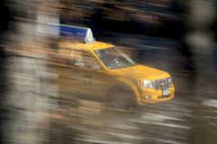 Yellow Taxi Cab at speed. A yellow taxi cab streaks along a street with blurred trees New York City, December , 2016 Royalty Free Stock Photos