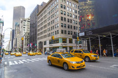 Yellow taxi cabs ride on 5th Avenue in New York City Stock Photo