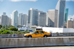 Yellow taxi car or vehicle. Miami, USA - December 17, 2015: yellow taxi car or vehicle for hire goes on highway or public road roadway in city with skyscrapers Royalty Free Stock Photography