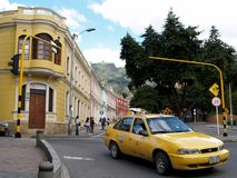 Yellow taxi and colonial buildings in Bogota, Colombia. Street signs and traffic Stock Photos