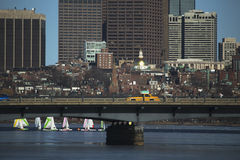 Yellow Taxi drives across Harvard Bridge over Charles River with Colorful sailboats, Boston, Massachusetts, USA Royalty Free Stock Photo