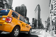 Yellow Taxi and Flatiron Building Royalty Free Stock Images