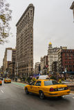 Yellow taxi and Flatiron building at Fifth Avenue av in Manhattan Stock Images