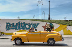 Yellow taxi in Havana, Cuba. Old american car serving as taxi for tourists, passing close a cuban government propaganda wall painting royalty free stock image